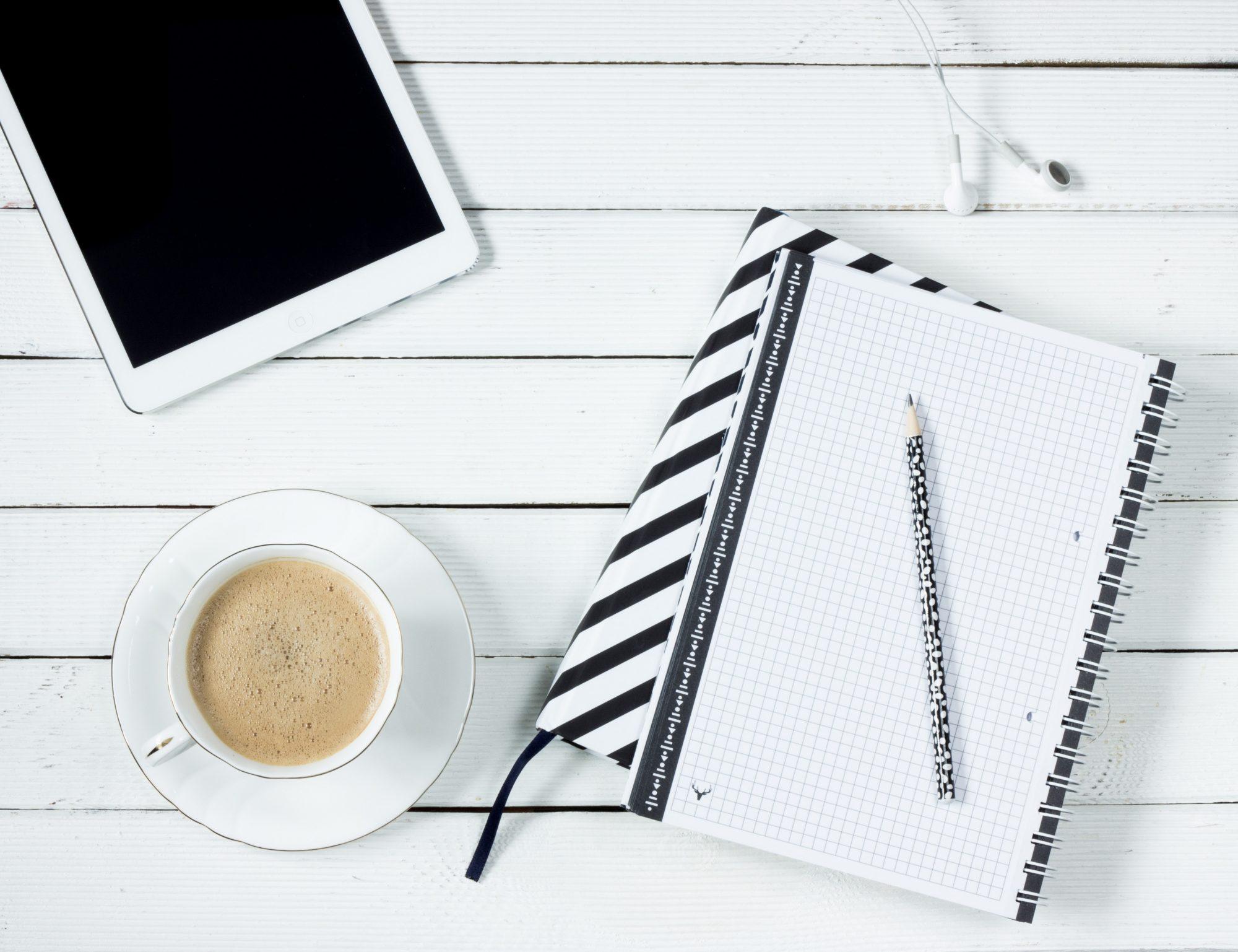 Notizblock, Ipad und Kaffe auf dem Tisch