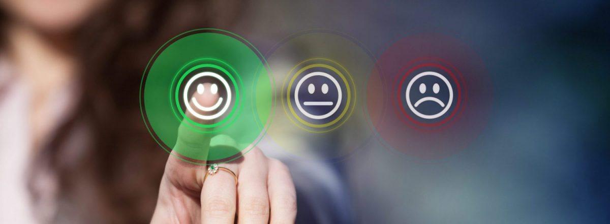 Zeigefinger auf grünen Smiley neben gelben und roten