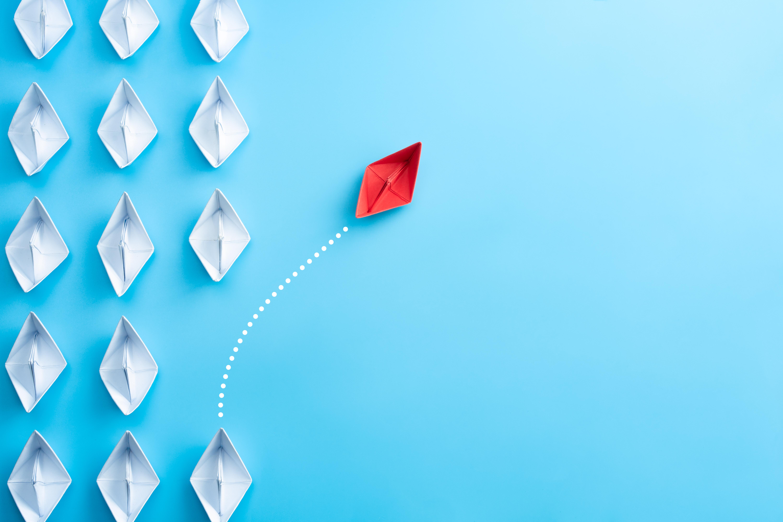 Change Management Rotes Papierboot tanzt aus der Reihe