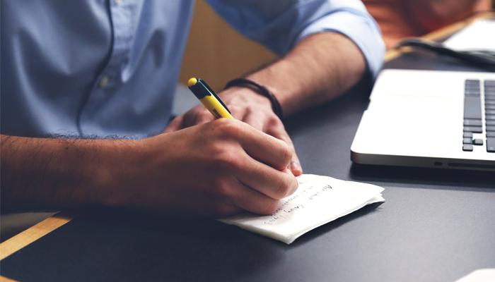 Mann schreibt etwas auf Zettel