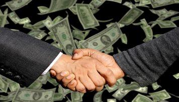 Handschlag mit Geld im Hintergrund