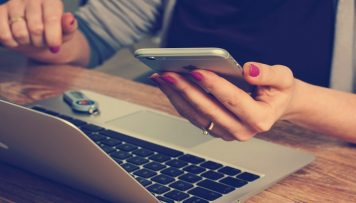 Frau mit mobilen Endgeraet und Laptop