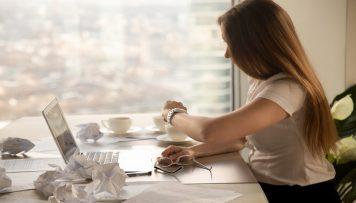 Online-Fragebogen auf die Uhr schauende Frau