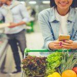 Lidl Frau mit mobilen Endgeraet und Einkaufswagen