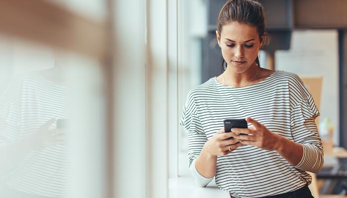 Frau steht vor dem Fenster mit Handy in der Hand