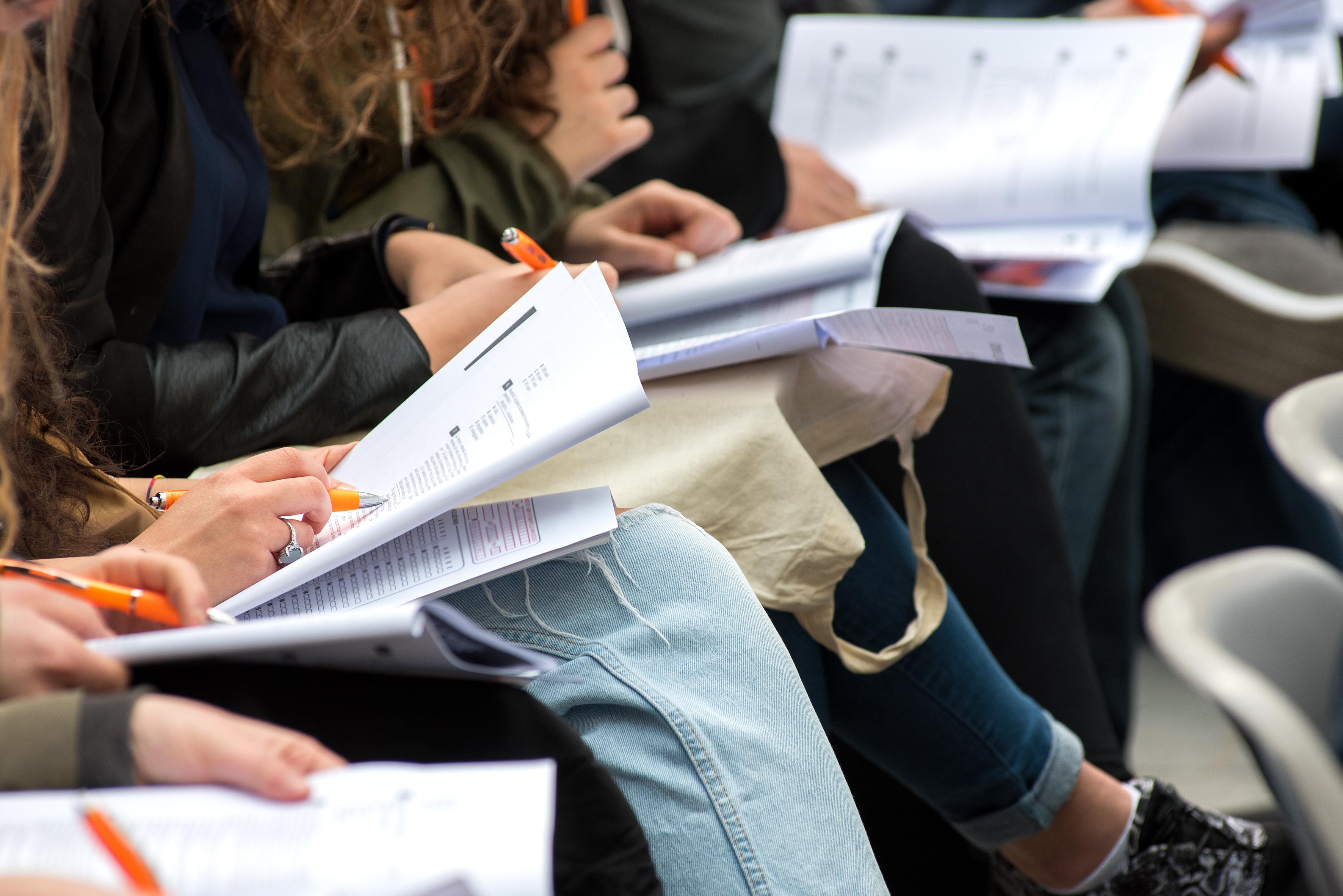 Paper-Pencil-Befragung Reihe Menschen mit Stift und Zettel