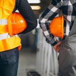 Mitarbeiterbefragung im Industriellen Bereich zwei orange Bauarbeiterhelme