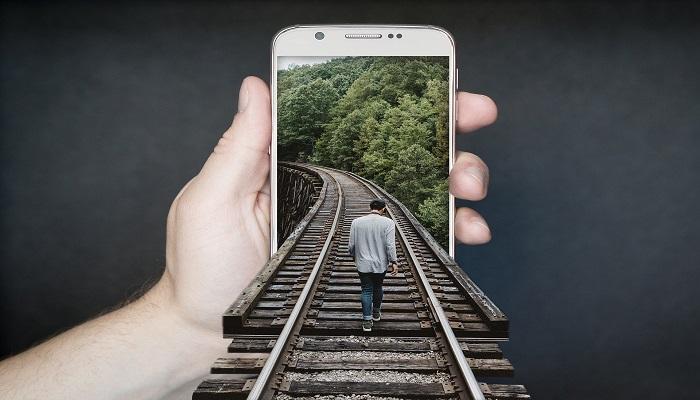 Person geht auf Gleis in Handybildschirm optische Täuschung