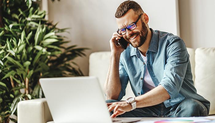 Mann auf Couch im Homeoffice mit Handy am Ohr vor Laptop