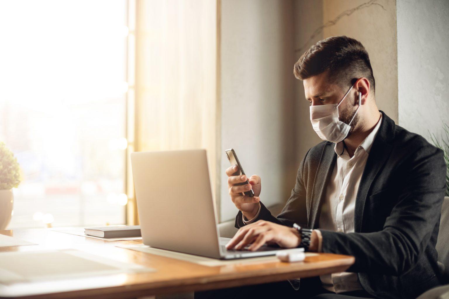 Mann mit Mundschutz, Anzug und Smartphone vor Laptop