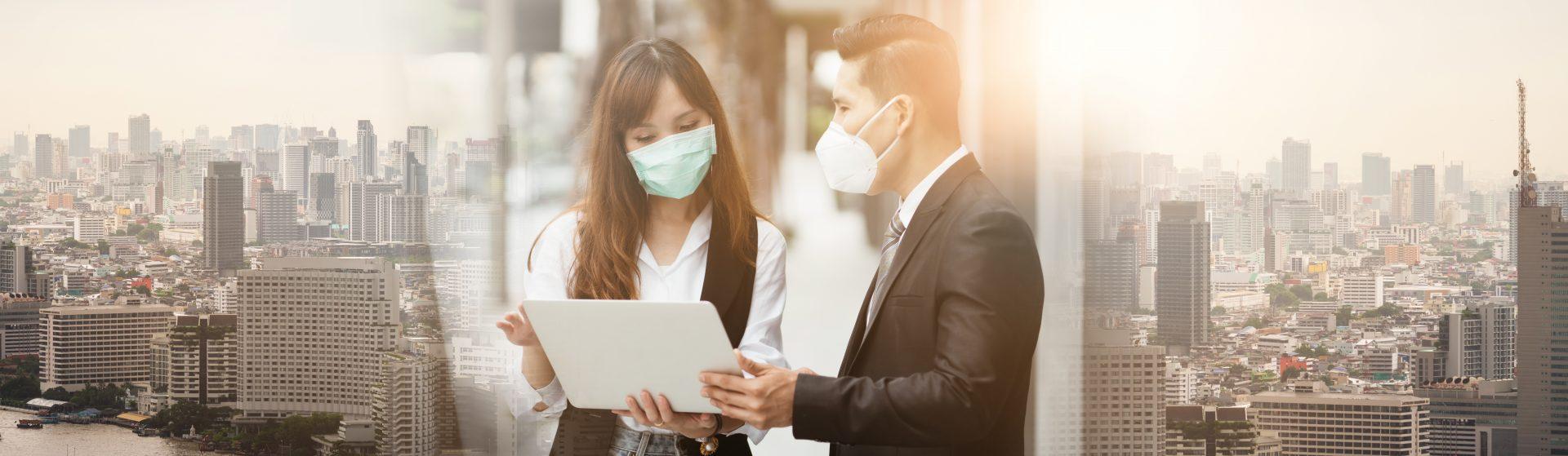 Zwei Menschen mit Atemschutzmaske vor Stadthintergrund