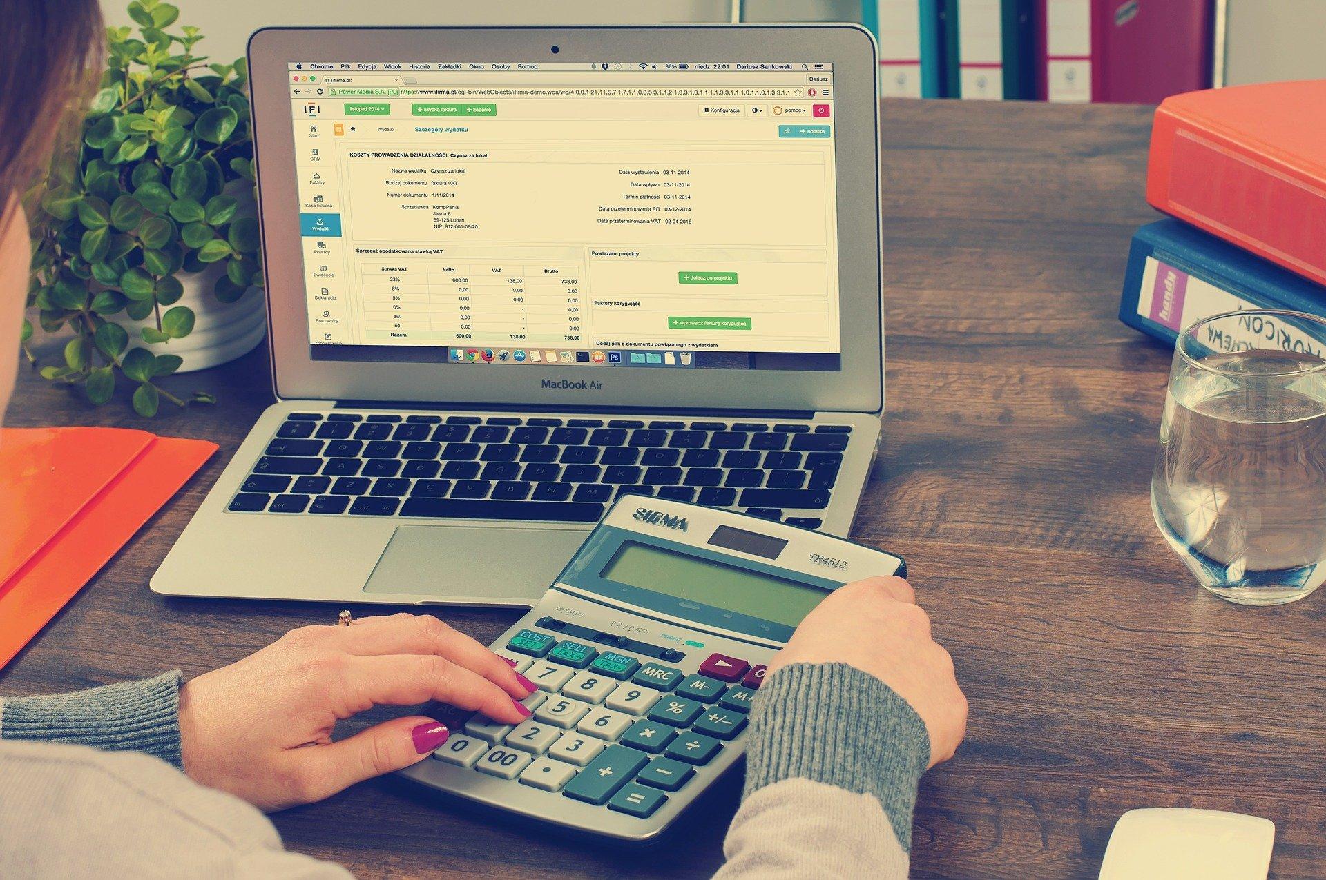 Frau rechnet mit Taschenrechner und Laptop Rücklaufquote