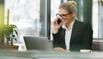 Blonde Frau telefoniert und surft am Laptop
