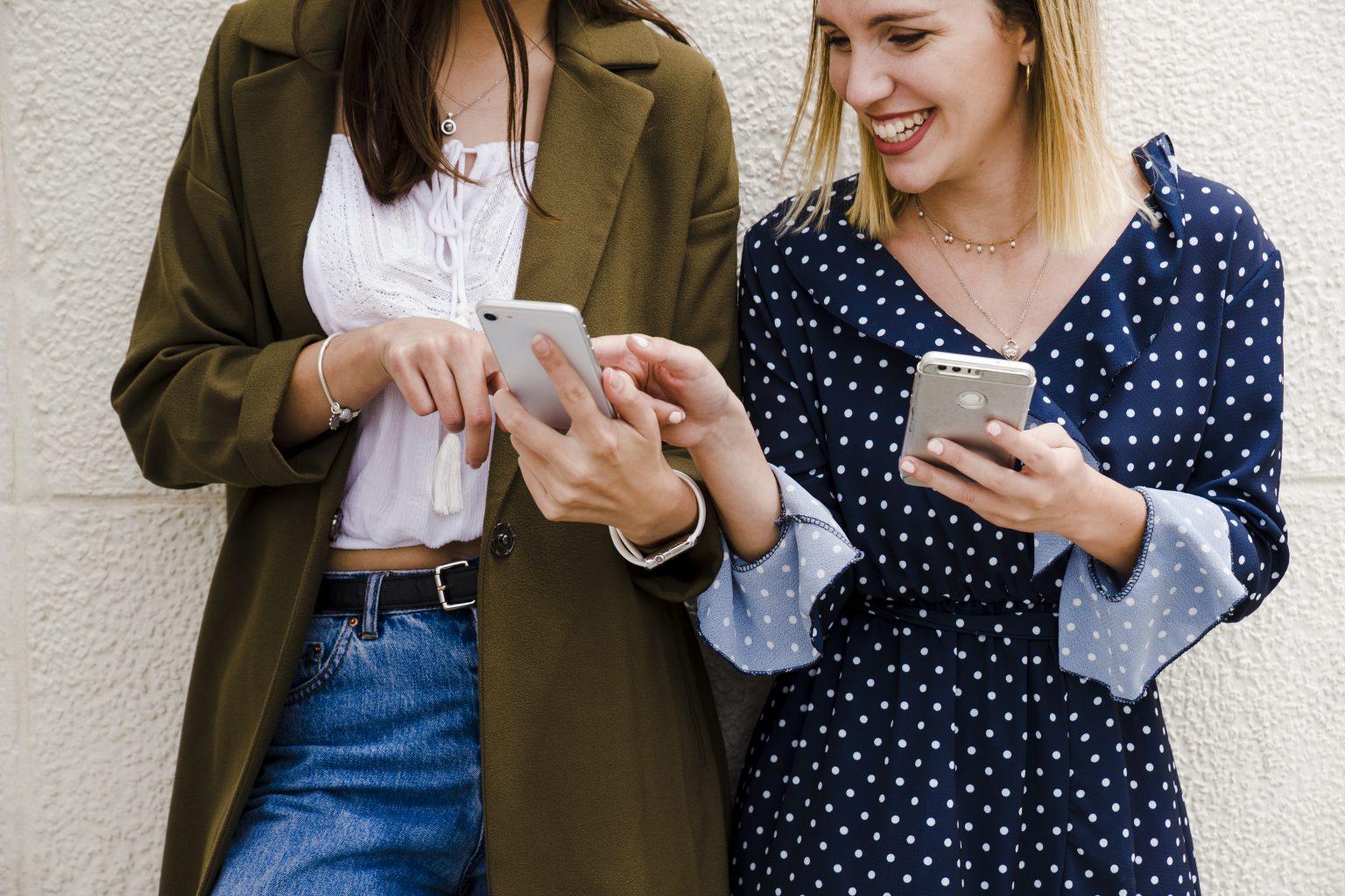 Freundinnen zeigen sich etwas auf dem Handy