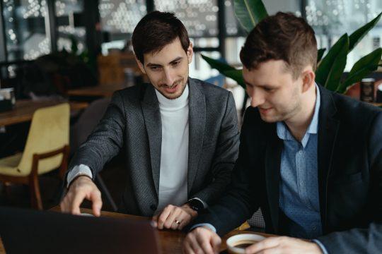 Geschäftsleute zeigen sich was auf dem Laptop