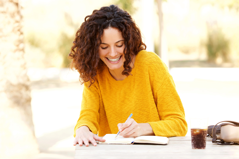 Junge Frau schreibt Tagebuch am Tisch Corona Diary
