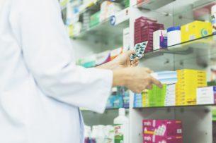 Apotheker mit Medikamenten in der Hand vor Regal Case Study