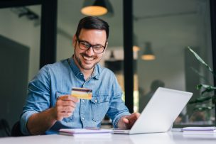 Mann mit Kreditkarte am Laptop