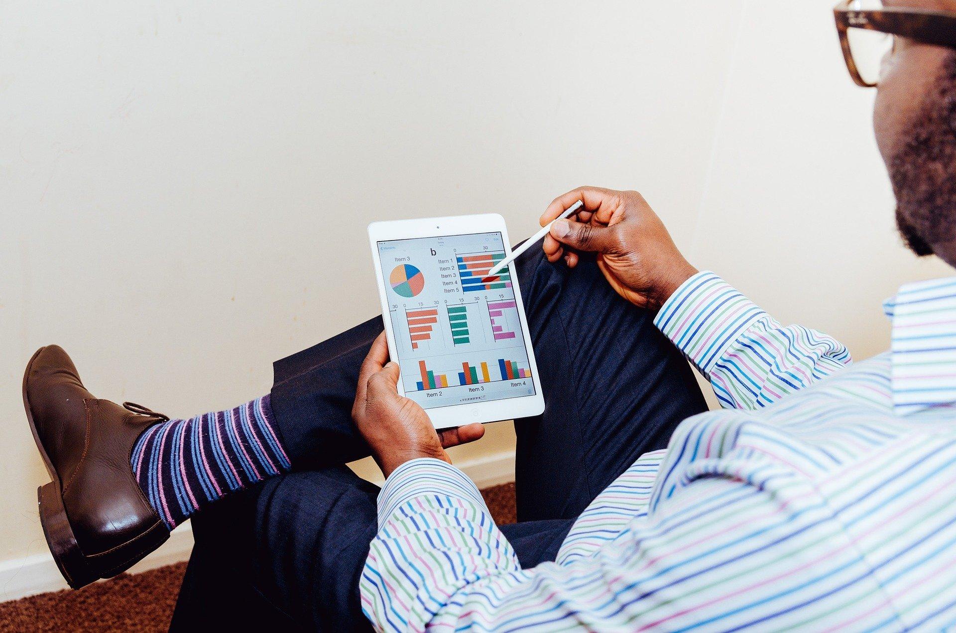 Mann zeigt mit Stift auf Tablet mit Diagrammen