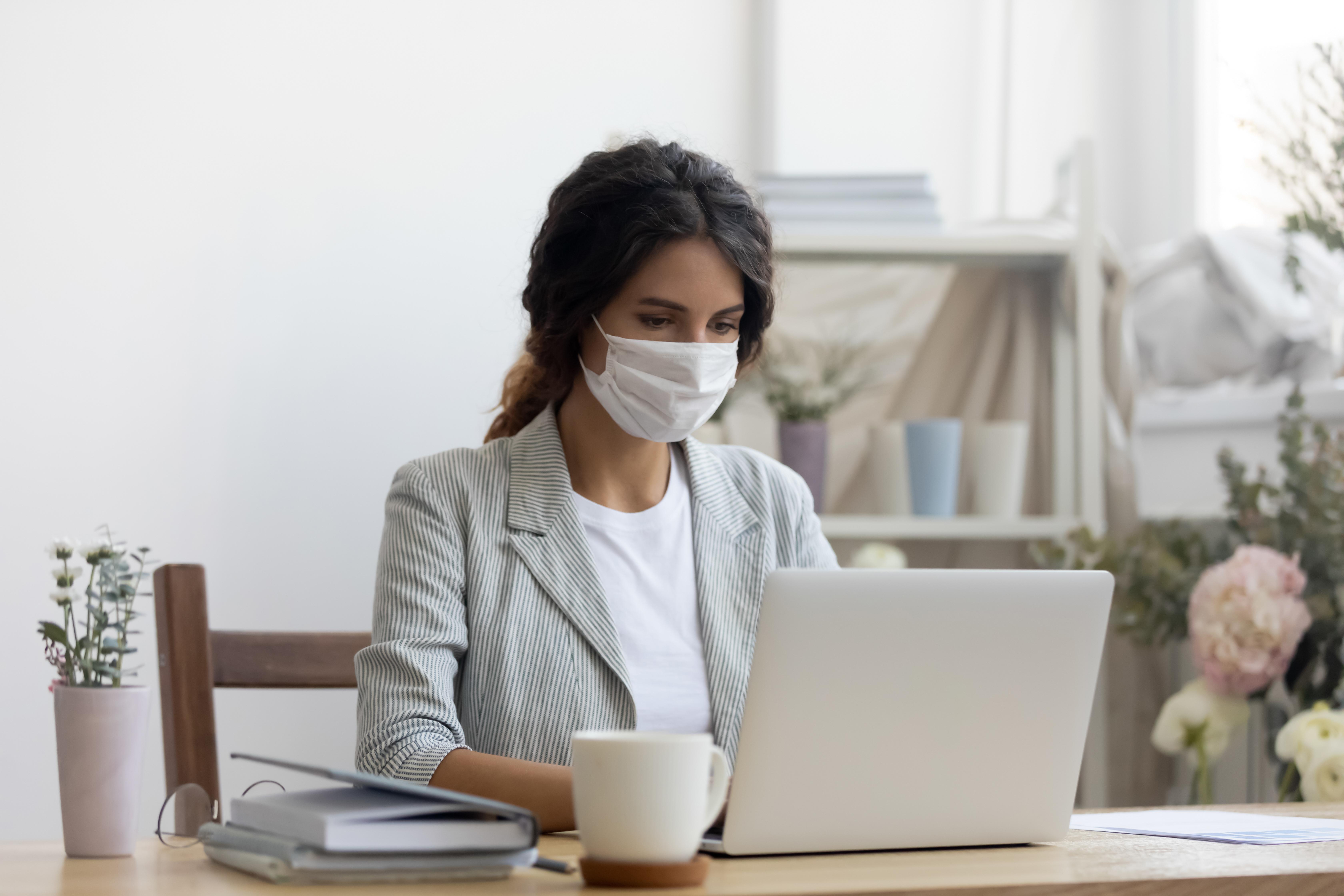 Frau arbeitet mit Maske im Büro