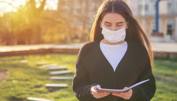 Frau mit Mundschutz und Buch draußen