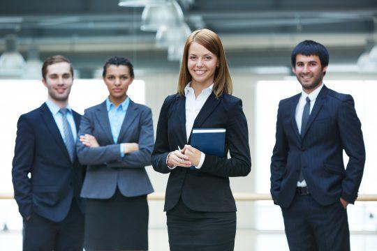 weiblicher Teamleader mit ihrem 3-köpfigen Team im Hintergrund
