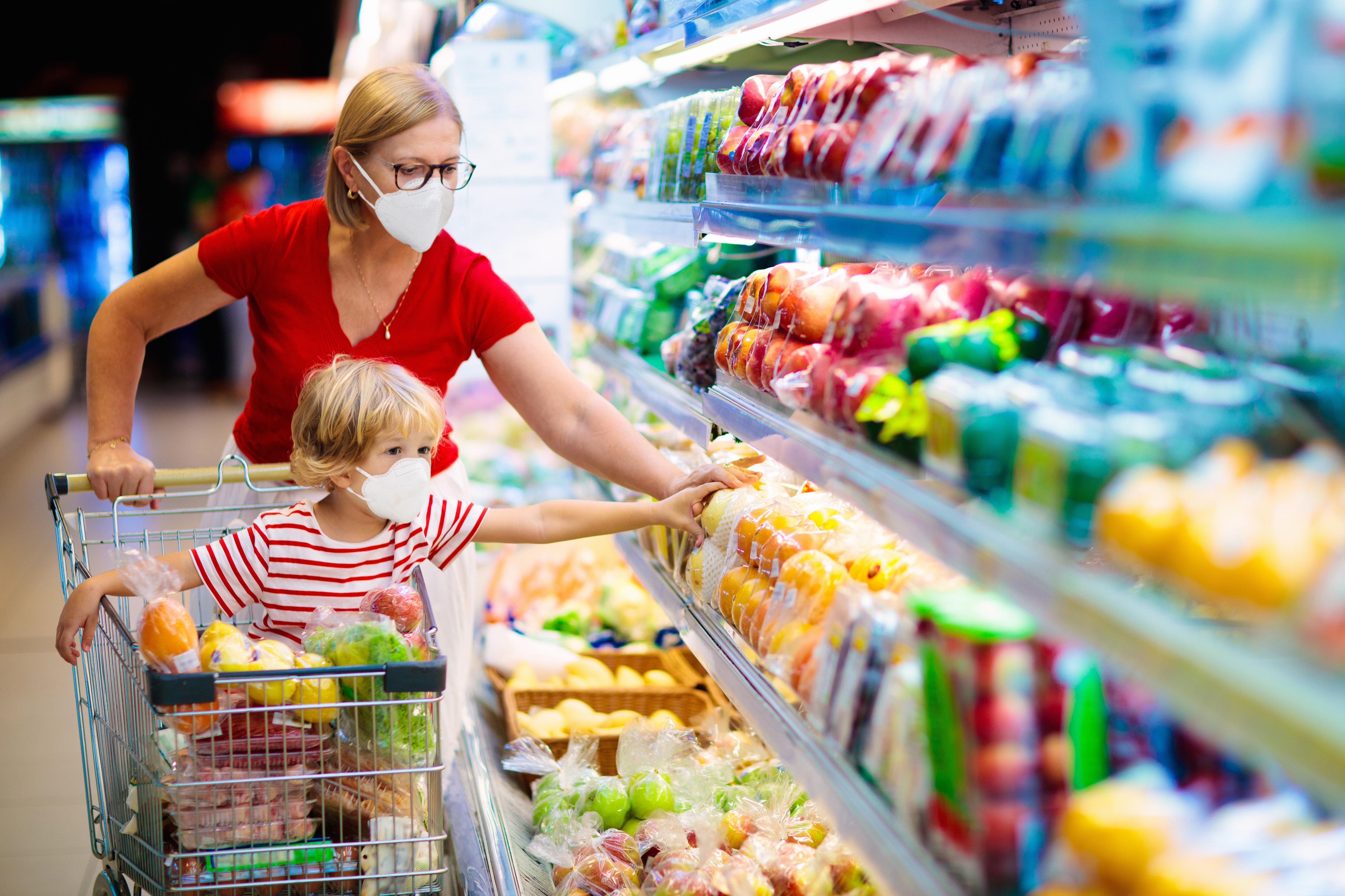 Mutter und Kind im Supermarkt während Corona-Krise