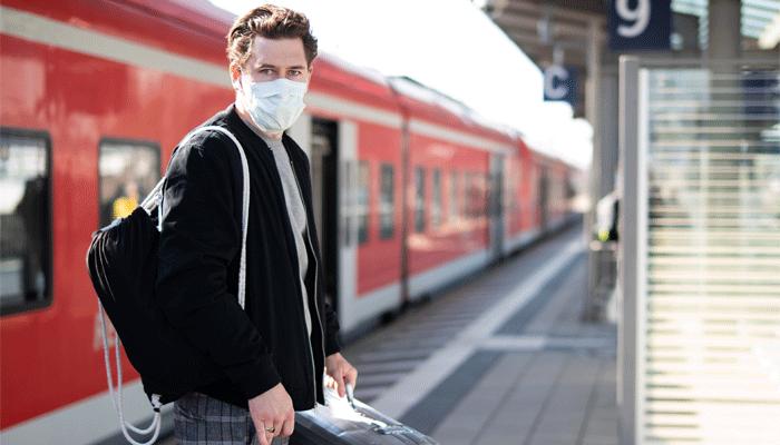 Mann mit Mundschutz am Bahnsteig DB