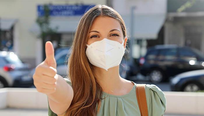 Covid-19 positive junge Frau mit Schutzmaske