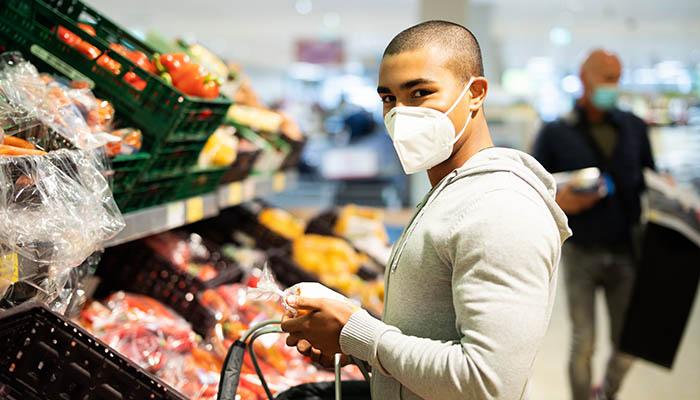 Einkaufen zur Zeit des Coronavirus, Mann mit Atemmaske in Supermarkt
