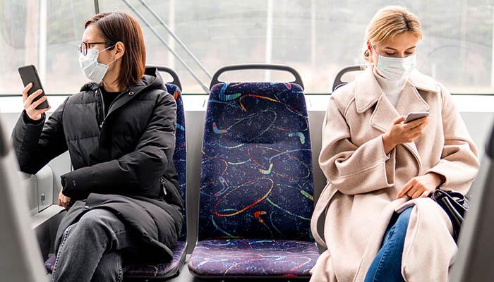 Junge Frauen im Bus auf dem Weg zur Arbeit während Corona-Krise