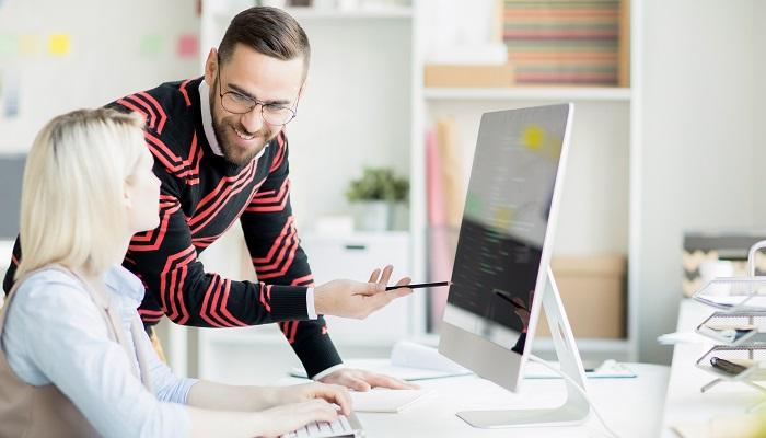 Zwei Kollegen beraten sich am PC