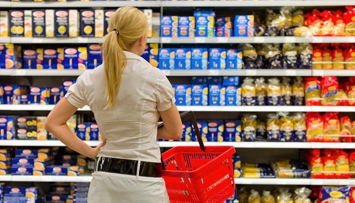 Frau steht vor einem Supermarktregal
