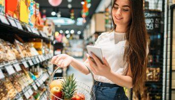Junge Frau beim Einkaufen schaut auf ihr Handy