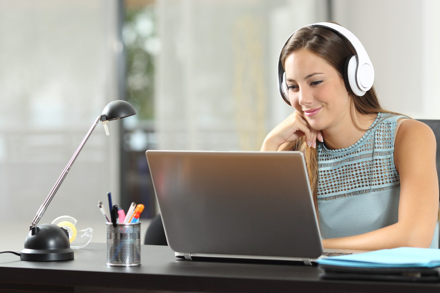 Frau am Laptop mit Kopfhörern Webinar