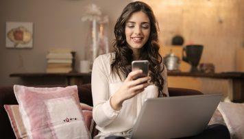 Junge Frau nutzt ihr Handy und hat Laptop auf dem Schoß