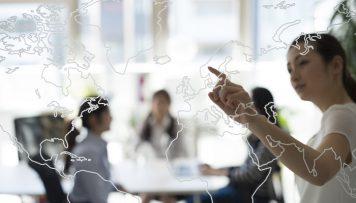 Frau zeigt mit dem Finger auf ein Weltkarte