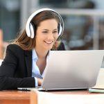 Frau mit Kopfhörern sitzt am Laptop und lacht