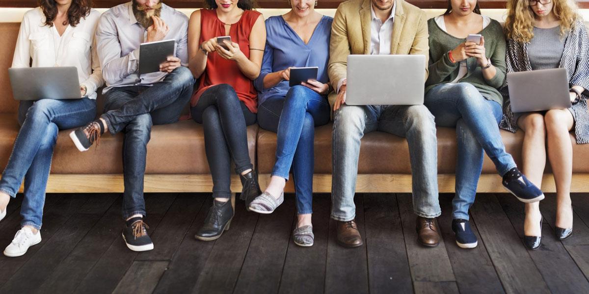 Gruppe sitzt in einer Reihe mit verschiedenen elektronischen Geräten in der Hand