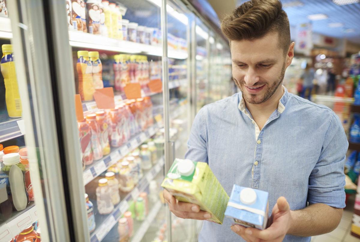 Mann entscheidet sich zwischen zwei verschiedenen Milchanbietern