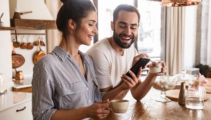 Paar beim Frühstück mit dem Handy