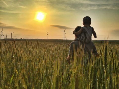 Windräder Sonnenuntergang Mann mit Kind auf Schultern im grünen Kornfeld