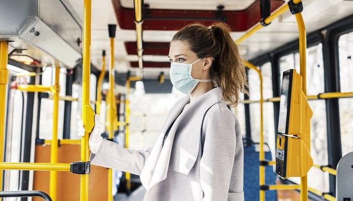 Frau mit Maske alleine im Bus