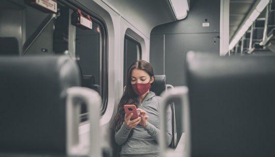 Junge Frau mit Maske sitzt alleine im Zug
