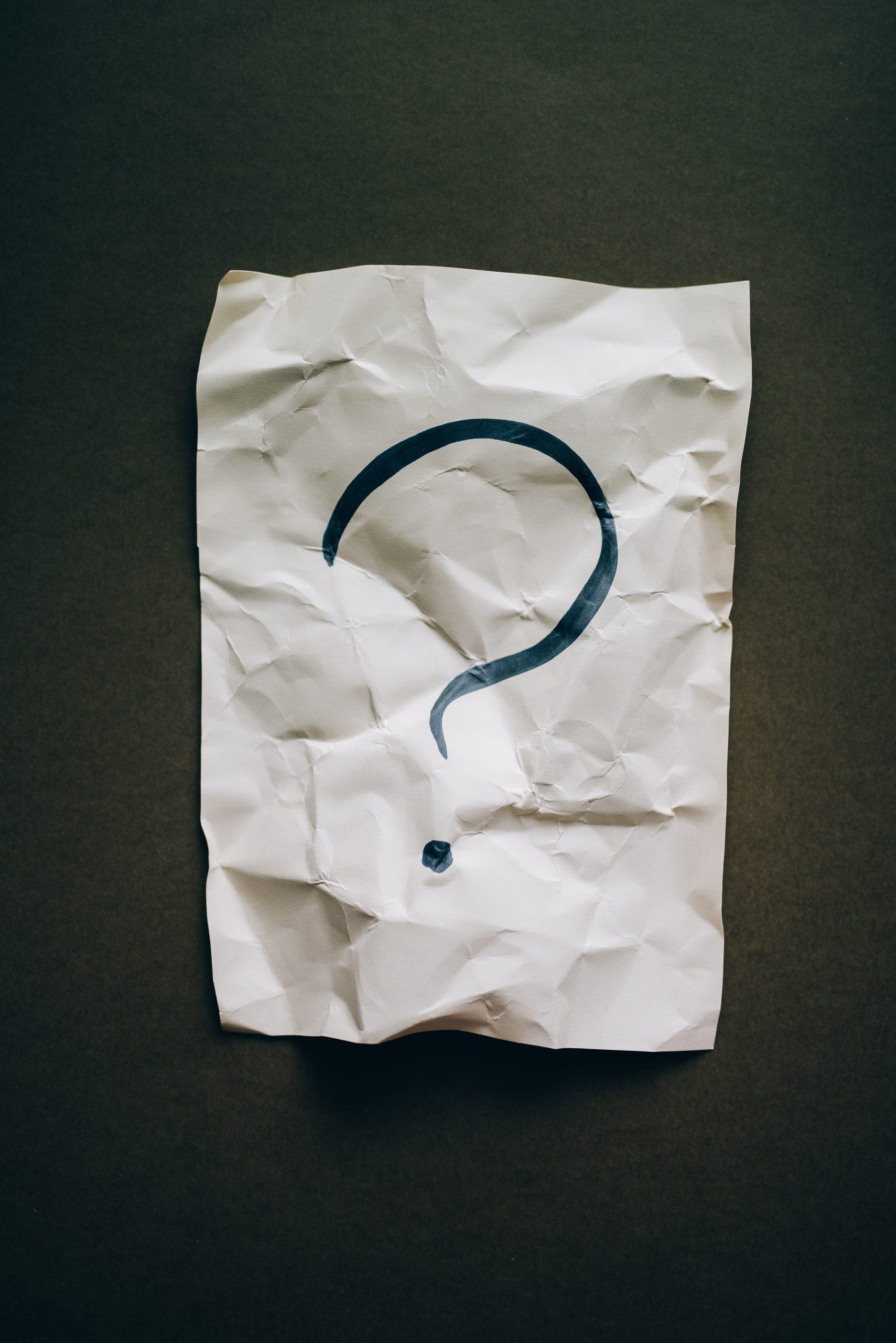Schwarzes Fragezeichen auf einem zerknitterten Papier