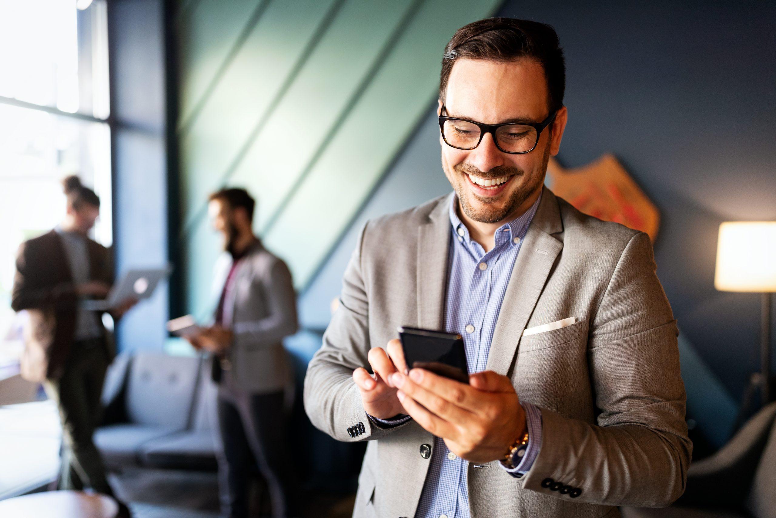 Geschäftsmann im grauen Anzug tippt auf sein Smartphone und lächelt dabei