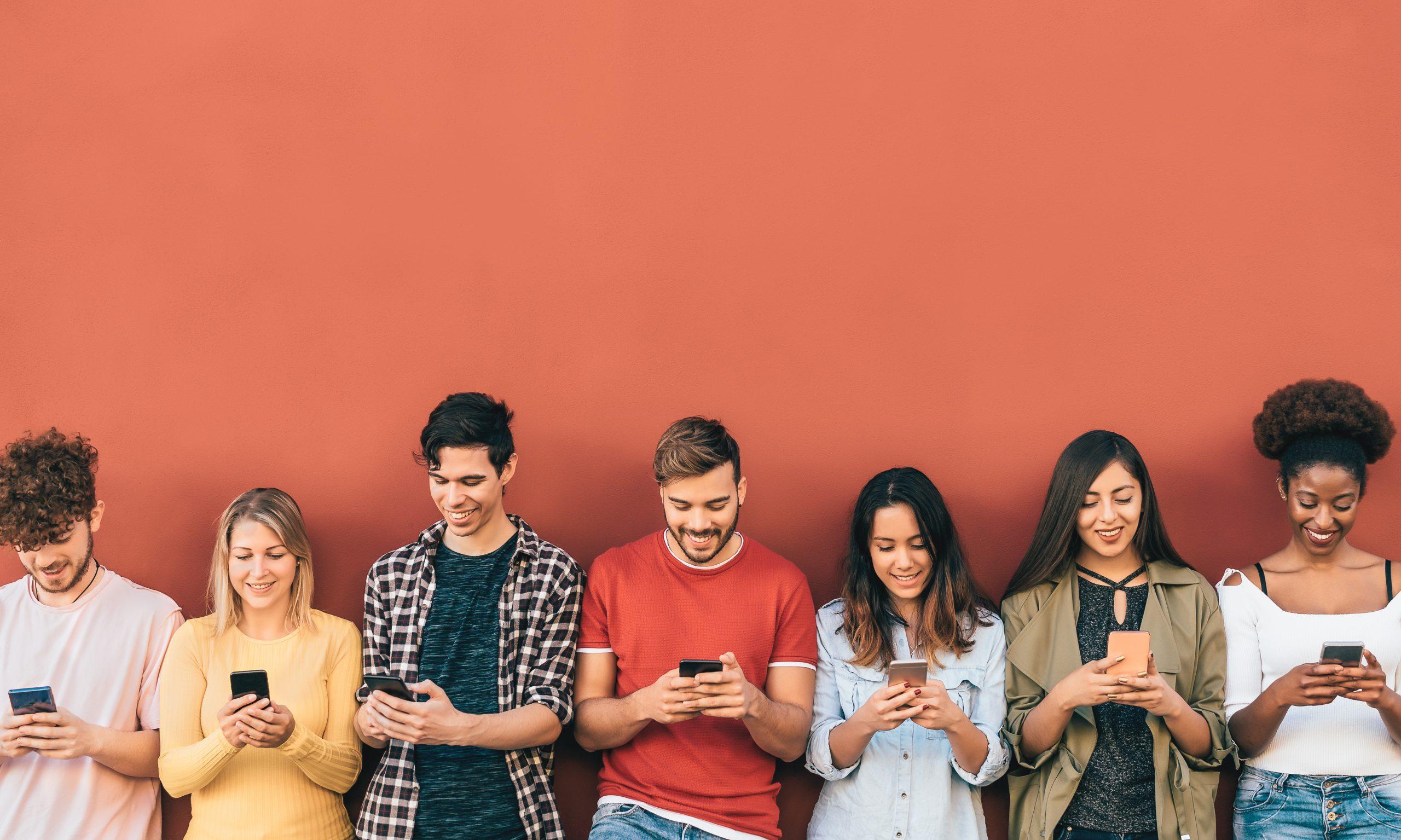 Junge Menschen mit Smartphone vor oranger Wand