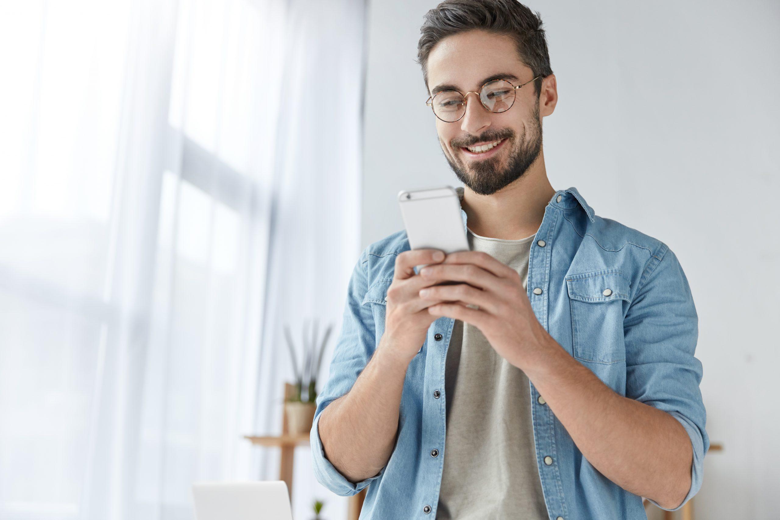 Glücklicher Mann tipp auf dem Handy