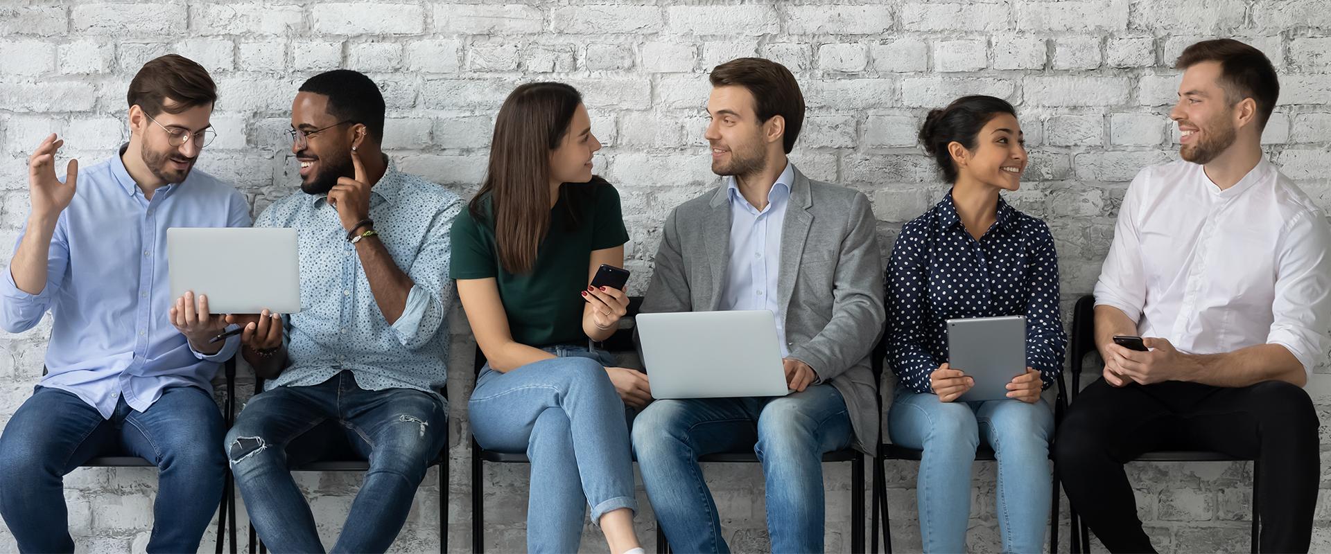 Junge Menschen auf Stühlen vor Wand mit Laptop und Handy