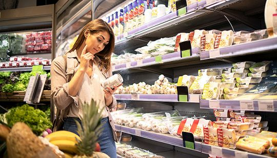 Woman in supermarket reading nutrition values from a product by the shelf.